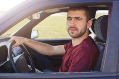 Ståenden av den attraktiva orakade mannen med ögonbrynremsan, rymmer handen på styrninghjulet, kör den svarta bilen, ser kameran  royaltyfri bild