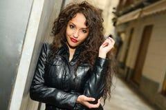 Attraktiv svart kvinna i stads- bakgrund som ha på sig läderjacke Royaltyfri Foto