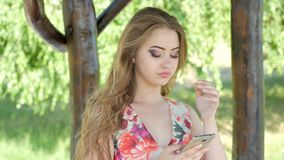 Ståenden av den avkopplade unga damen i en sommar parkerar att läsa ett textmeddelande på hennes mobiltelefon lager videofilmer