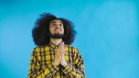 Ståenden av den be afrikansk amerikangrabben som håller fingrar korsade och skriker guden, behar på blå bakgrund Begrepp av lager videofilmer