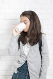 Ståenden av den bleautiful unga asiatiska flickan rymmer ett exponeringsglas av vatten I royaltyfri fotografi