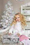 Ståenden av den blonda lilla flickan sitter på en soffa och trycker på en gåvaask i jul royaltyfri fotografi