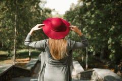 Ståenden av den blonda modellen som bär den röda hatten, och grå färger sticker klänningen på Royaltyfria Foton