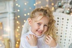 Ståenden av den blonda nätta lilla flickan ler mycket i tröja i jul arkivfoton