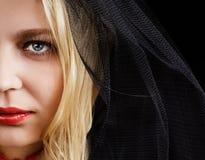 Ståenden av den blonda unga kvinnan i en svart skyler Arkivfoto