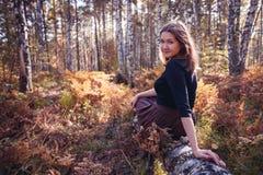 Ståenden av den bruna haired flickan i skogen i solljus, höstnedgångbegrepp i hösten parkerar skjutit utomhus- för ö för fall dim royaltyfri bild