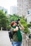 Ståenden av den caucasian kvinnan för den vuxna rödhåriga mannen i tillfällig kläder med hennes reflex DSLR som tar bilder i stad fotografering för bildbyråer