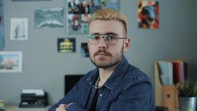 Ståenden av den caucasian stiliga mannen med exponeringsglas och gult hår för stilfull frisyr som sitter det hemmastadda kontorss arkivfilmer
