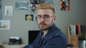 Ståenden av den caucasian stiliga mannen med exponeringsglas och gult hår för stilfull frisyr som sitter det hemmastadda kontorss lager videofilmer