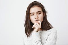 Ståenden av den drömlika mjuka flickan med fundersamt uttryck som rymmer handen nära, skvallrar medan det stickande fingret och a arkivfoton