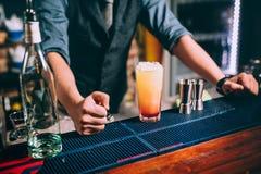 Ståenden av den elegant och tappningbartendern, bartendern som förbereder apelsinen, baserade vodka- och tequilacoctailar arkivfoto