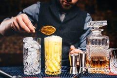 Ståenden av den elegant och tappningbartendern, bartendern som förbereder apelsinen, baserade vodkacoctailar royaltyfri bild