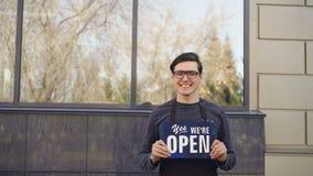 Ståenden av den gladlynta unga mannen i förklädet som sköter om hållande ` för företagsägaren ja är vi, det öppna `-teckenanseend arkivfilmer