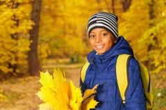Ståenden av den gulliga afrikanska pojken med sidor samlar ihop Fotografering för Bildbyråer