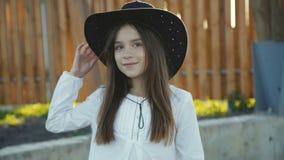 Ståenden av den gulliga flickan i hatt ler på kameran på kapplöpningsbanan lager videofilmer