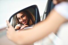 Ståenden av den gulliga le flickan sitter i bilen och ser bilspegeln royaltyfria foton