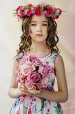 Ståenden av den gulliga lilla flickan i trevlig vårklänning, med den blommiga kransen på huvudet, rymmer buketten av blommor Arkivfoto