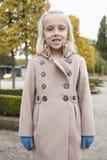 Ståenden av den gulliga lilla flickan i vinterlaganseende på parkerar Royaltyfri Bild