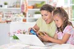 Ståenden av den gulliga lilla flickan med barn fostrar att spela datoren royaltyfri fotografi