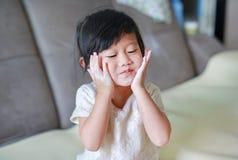 Ståenden av den gulliga lilla flickan med behandla som ett barn pulver på hennes framsida Lilla flickan häller talken till handen fotografering för bildbyråer