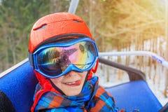 Ståenden av den gulliga skidåkarepojken i en vinter skidar semesterorten arkivbild