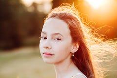 Ståenden av den härliga allvarliga tonåriga flickan tycker om naturen i parkerar på sommarsolnedgången royaltyfri bild