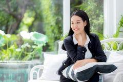 Ståenden av den härliga asiatiska affärskvinnan med att le och kopplar av sammanträde på soffan Arkivbild