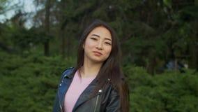 Ståenden av den härliga asiatiska flickan som in ler, parkerar stock video