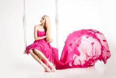 Ståenden av den härliga blonda flickan på gunga i ljusa rosa färger klär royaltyfri foto