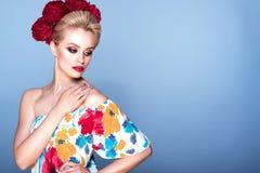 Ståenden av den härliga blonda modellen med updohår och det perfekta ljusa sminket som bär blom- sundress och den fluffiga pionen Royaltyfria Foton