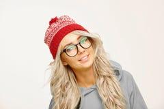 Ståenden av den härliga caucasian kvinnan med långt blont hår, bär runda anblickar, rött lock, har ett gulligt leende, att isoler arkivfoto