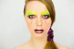Ståenden av den härliga flickan med idérikt smink med blänker arkivbilder