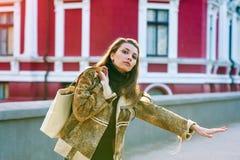 Ståenden av den härliga flickan med långt hår står i gatan med en påse Arkivbilder