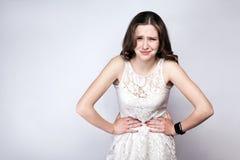 Ståenden av den härliga kvinnan med fräknar och vit klär och ilar klockan med magen smärtar på silvergrå färgbakgrund royaltyfri fotografi