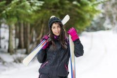 Ståenden av den härliga kvinnan med skidar och skidar dräkten i vinterberg Arkivfoto