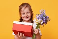 Ståenden av den härliga lilla flickan med den röda gåvan och buketten av blåa florets som förbereder sig för mors dag, önskar att royaltyfria foton