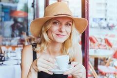 Ståenden av den härliga mitt för mode åldrades kvinnan i kafé med koppen kaffe, lyckligt leende royaltyfria bilder