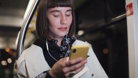 Ståenden av den härliga unga kvinnan i hörlurar som offentligt rider transport, lyssnar musik och bläddra på guling arkivfilmer