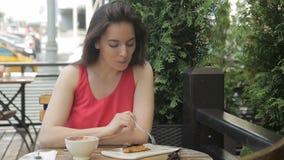 Ståenden av den härliga unga kvinnan som sitter i det utomhus- kafét och äter kakan vid gaffeln arkivfilmer
