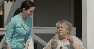 St?enden av den h?ga kvinnan som tar pillersjuksk?terskan ger medicin som tillsammans ler p? v?rdhemdet fria p? Sunny Day Shot p? stock video