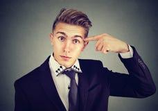 Ståenden av den ilskna tokiga unga mannen som gör en gest med fingret som frågar, är dig som är galen? arkivbilder
