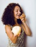 Ståenden av den isolerade unga gulliga kvinnan göra val mellan äpplet och candys, bantar folklivsstilbegrepp Fotografering för Bildbyråer