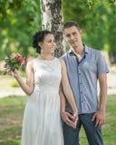 Ståenden av den kvinnliga bruden för härliga barnpar med små brölloprosa färger blommar rosbuketten och manbrudgumanseendet och h royaltyfria foton