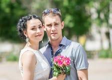 Ståenden av den kvinnliga bruden för härliga barnpar med små brölloprosa färger blommar rosbuketten och manbrudgummen, att le och arkivfoton