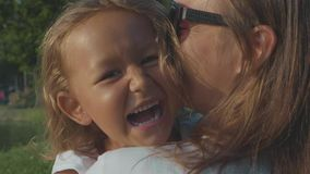 Ståenden av den lilla skratta barnflickan i hennes moder` s kramar utomhus- lager videofilmer