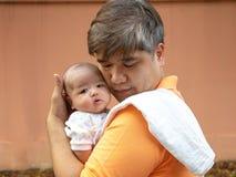 Ståenden av den lyckliga Asien fadern som rymmer hans nyfödda sötsak, behandla som ett barn kläder för iklädd vit Omfamna för fad Royaltyfria Bilder