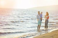 Ståenden av den lyckliga familjen och behandla som ett barn tycka om solnedgång i sommarfritiden royaltyfri bild
