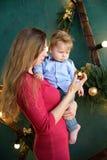 Ståenden av den lyckliga familjmodern och behandla som ett barn den lilla sonen som hem spelar på julferier, ` s för det nya året Royaltyfria Foton