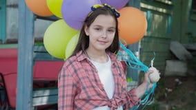 Ståenden av den lyckliga flickan poserar med ballonger utomhus på kameran arkivfilmer