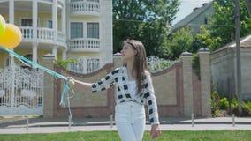 Ståenden av den lyckliga flickan poserar med ballonger utomhus på kameran stock video
